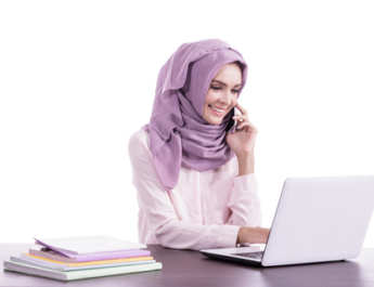 college student wearing hijab applying for colleges on laptop computer while talking on mobile phone isolated on white background